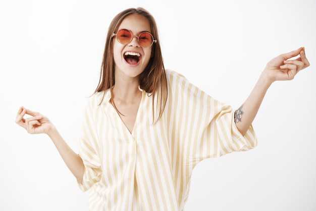 portrait-joyful-happy-amused-carefree-stylish-woman-trendy-red-sunglasses-yellow-striped-blouse-dancing-singing-song-out-loud-with-broad-smile-hands-spread-aside_176420-23690